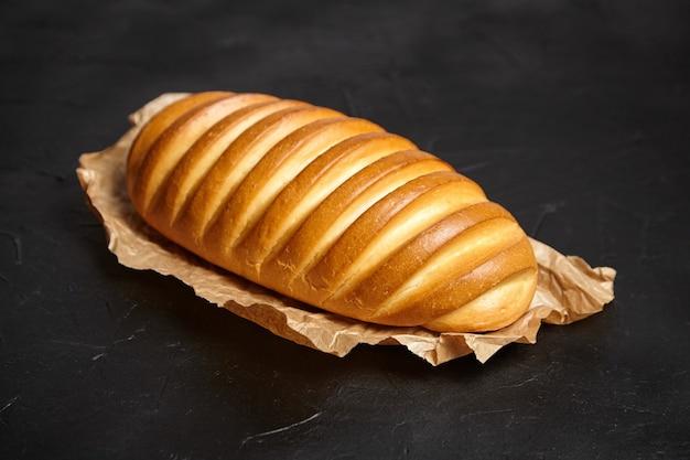 Gebakken hele broodje op donkere stenen tafel. brood, wit tarwebrood op bakpapier op zwarte achtergrond