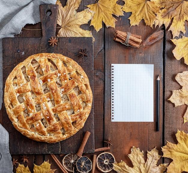 Gebakken hele ronde appeltaart op een bruin houten bord