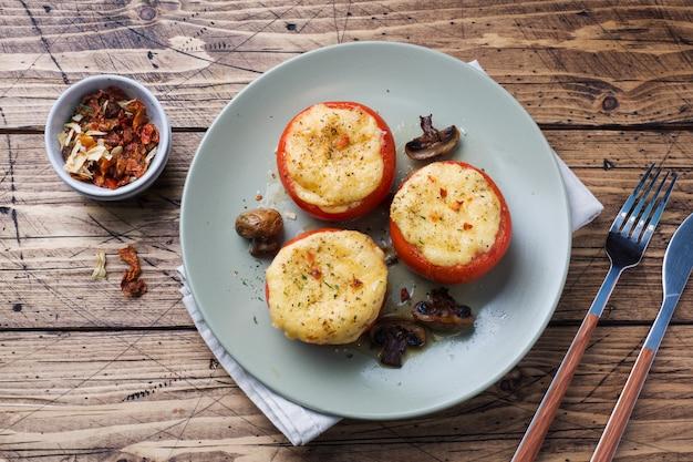 Gebakken hele tomaten gevuld met champignons en kaas met kruiden. kopieer ruimte.