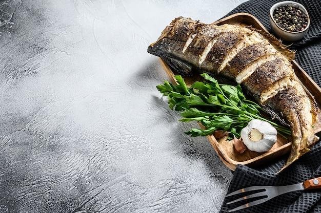 Gebakken hele vis schelvis op een snijplank. grijze achtergrond
