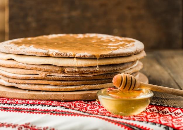 Gebakken honing cakes voor de cake in een stapel op een houten tafel.