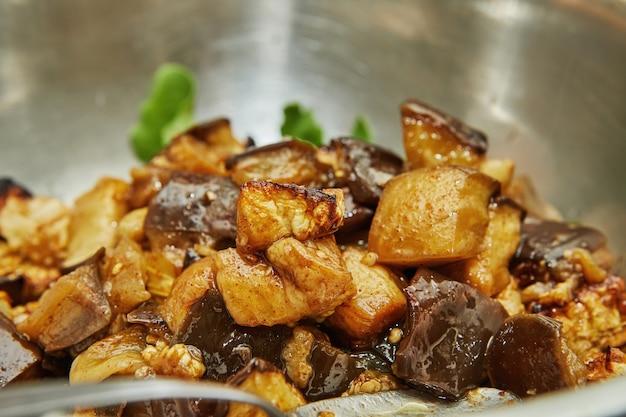 Gebakken, in blokjes gesneden aubergine in kom rucola. stap voor stap recept.