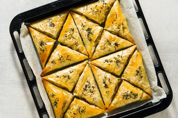 Gebakken in de oven indiase samosa gemaakt met filodeeg met pittige aardappelen en groenten met zwarte sesamzaadjes. straat traditioneel fastfood