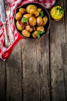 Gebakken in pan hele jonge aardappelen, zelfgemaakte vegetarische gerechten, houten oude rustieke tafel, met saus, hierboven