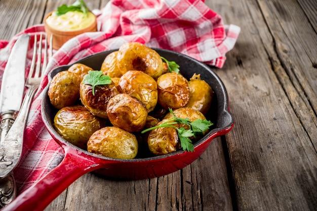 Gebakken in pan hele jonge aardappelen, zelfgemaakte vegetarische gerechten, houten oude rustieke tafel, met saus, kopie ruimte