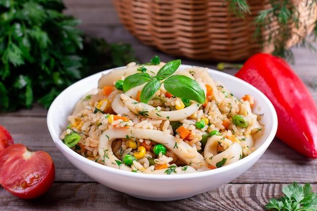 Gebakken inktvis met rijst en groenten in een kom