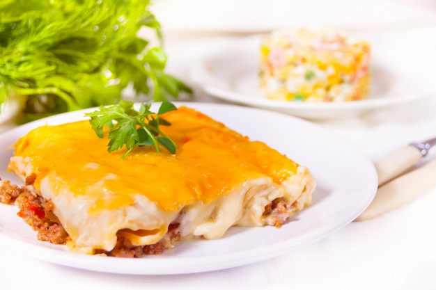 Gebakken italiaanse cannelloni met gehakt met bechamelsaus op de witte plaat.