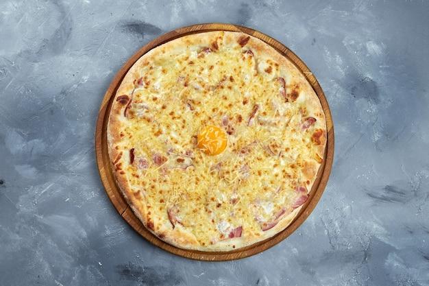 Gebakken italiaanse pizza met dooier, parmezaanse kaas, spek en romige saus op een houten dienblad op een grijze achtergrond. pizza carbonara