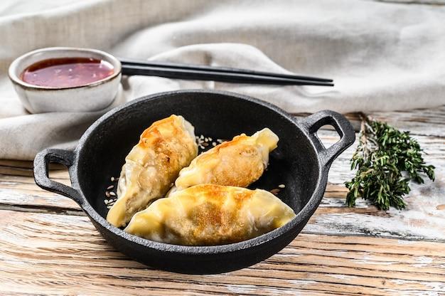 Gebakken japanse gyoza-dumplings in een pan. witte houten achtergrond. bovenaanzicht.