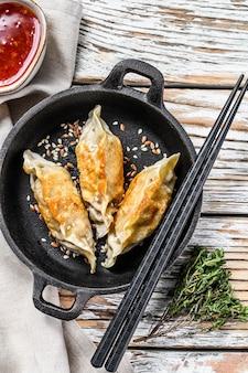 Gebakken japanse gyoza dumplings in een pan. witte houten ruimte. bovenaanzicht