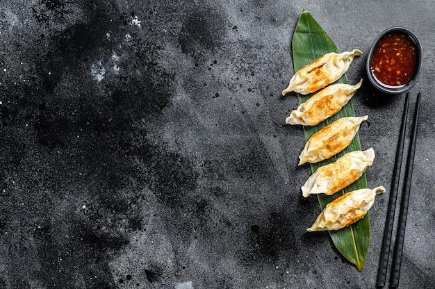 Gebakken japanse gyoza dumplings. zwarte ruimte. bovenaanzicht. kopieer ruimte