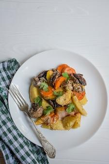 Gebakken jonge aardappelen met vlees en groenten. donkere houten achtergrond.