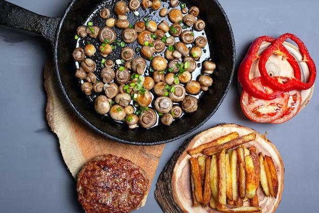 Gebakken junkfood bovenaanzicht. zelfgemaakte calorierijke keuken: champignons, aardappel, kotelet met groenten plat leggen.