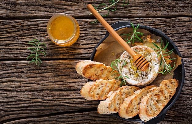 Gebakken kaas camembert met rozemarijn en honing. smakelijk eten. bovenaanzicht plat leggen