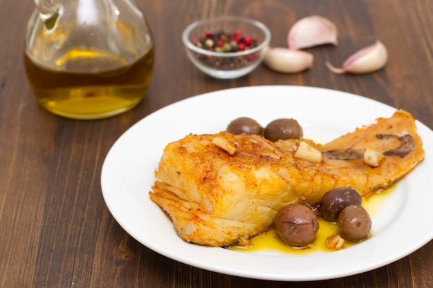 Gebakken kabeljauwvis met knoflook en olijfolie op schotel