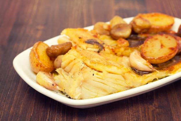 Gebakken kabeljauwvissen met kastanjes en aardappel op witte schotel