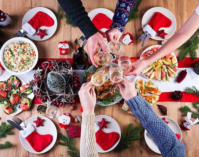 Gebakken kalkoen. kerstdiner. de kersttafel wordt geserveerd met een kalkoen, versierd met helder klatergoud en kaarsen. gebakken kip, tafel. familie diner. bovenaanzicht, handen in het frame