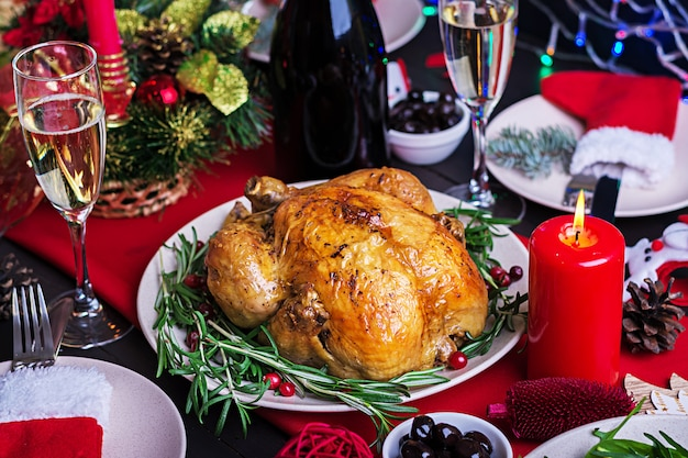 Gebakken kalkoen. kerstdiner. de kersttafel wordt geserveerd met een kalkoen, versierd met helder klatergoud en kaarsen. gebakken kip, tafel. familie diner.