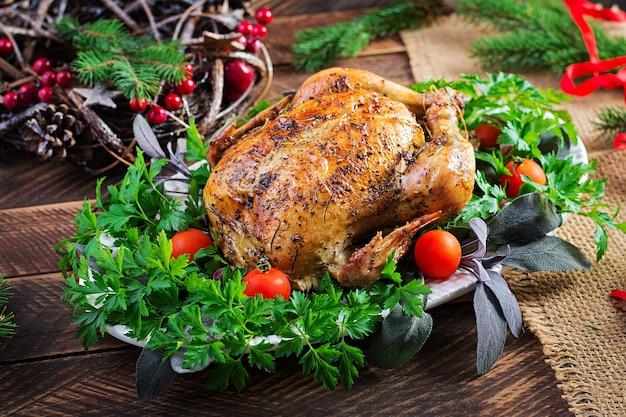 Gebakken kalkoen of kip. de kersttafel wordt geserveerd met een kalkoen, versierd met helder tinsel. gebakken kip, tafelschikking. kerstdiner.