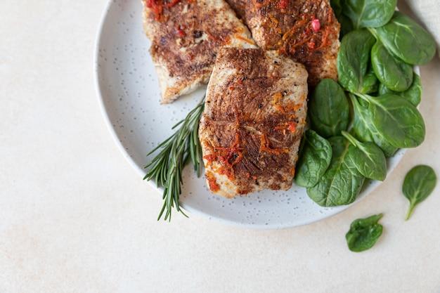 Gebakken kalkoen of kipfilet geserveerd met sinaasappelsaus, spinazie en rozemarijn. gezond uitgebalanceerd eten