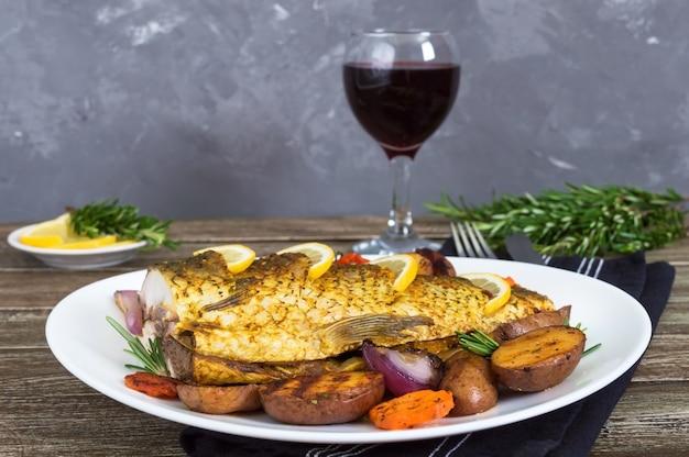 Gebakken karper met groenten gegrild op een witte plaat en een glas rode wijn op een houten achtergrond.