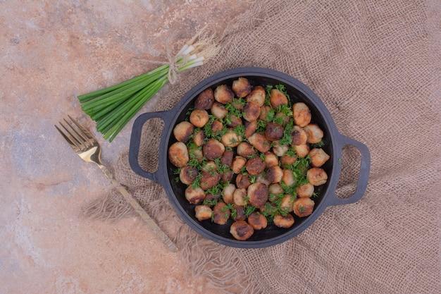 Gebakken khinkali in een zwarte pan met gehakte kruiden.