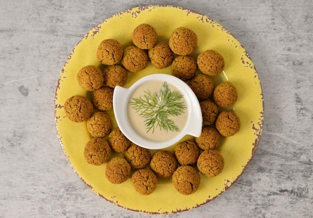 Gebakken kikkererwten falafel ballen op gele plaat op grijs, gezond en veganistisch eten met tahini diep, traditionele mediterrane, bovenaanzicht, plat leggen met kopie ruimte