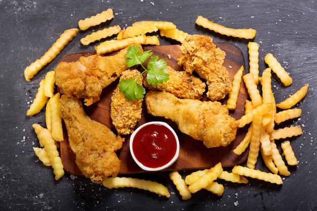 Gebakken kip en frietjes op een donkere tafel, bovenaanzicht