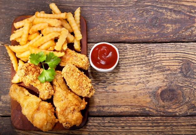 Gebakken kip en frietjes op een houten tafel, bovenaanzicht