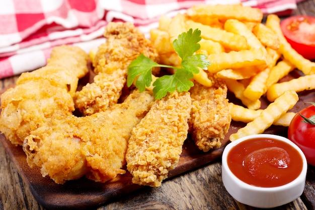 Gebakken kip en frietjes op een houten tafel