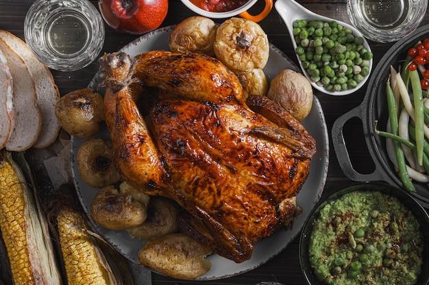 Gebakken kip en gebakken maïs. familie eettafel. gebakken kip en groenten met glazen cider. heerlijk rustiek diner