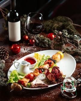 Gebakken kip en groenten op stok met glas rode wijn