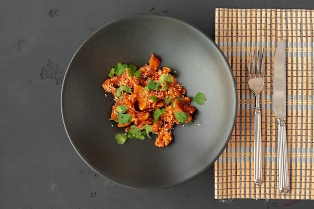 Gebakken kip en pinda's met saus in zwarte keramische kom bovenaanzicht