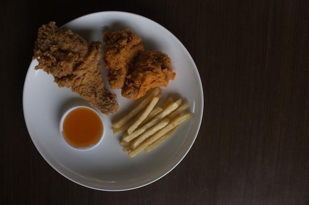 Gebakken kip gebakken frieten op een witte plaat bovenaanzicht weinig licht of onderbelicht