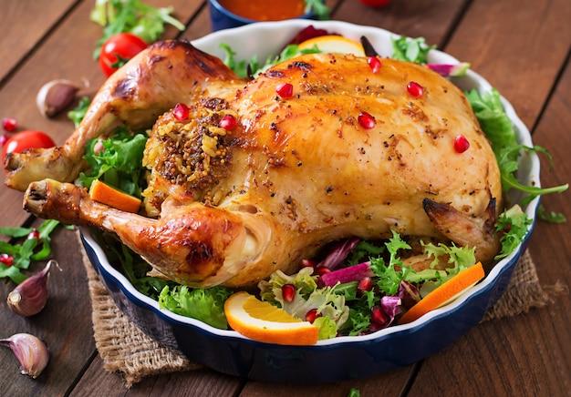 Gebakken kip gevuld met rijst voor thanksgiving-diner op een feestelijke tafel