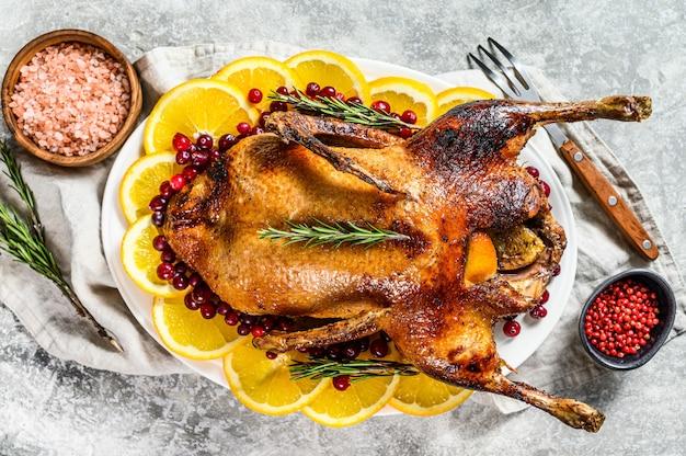 Gebakken kip gevuld met sinaasappels en rozemarijn. feestelijke tafel.