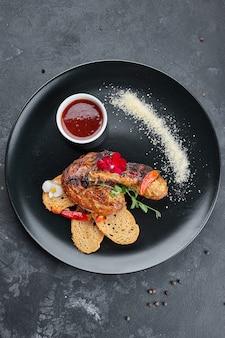 Gebakken kip, met croutons en saus, op een zwarte achtergrond