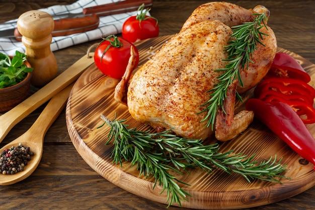 Gebakken kip met een gouden korst met groenten en kruiden op een houten ondergrond.