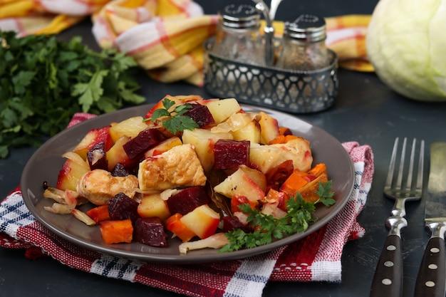 Gebakken kip met groenten: bieten, wortelen, kool en aardappelen