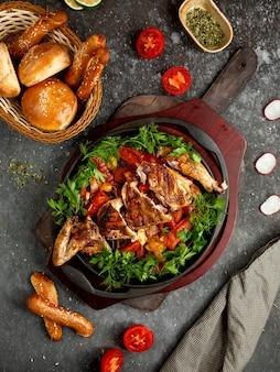 Gebakken kip met groenten en kruiden in een aluminium koekepan