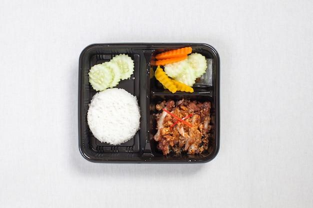 Gebakken kip met knoflook en peper en rijst in zwarte plastic doos, op een wit tafelkleed, voedseldoos, thais eten.