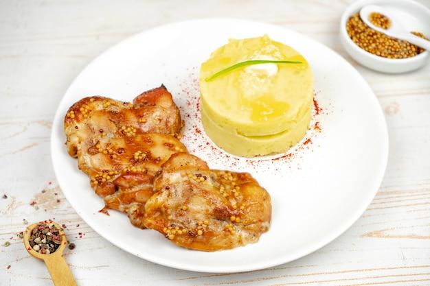 Gebakken kip met mosterd en honingsaus met aardappelpuree op een witte plaat