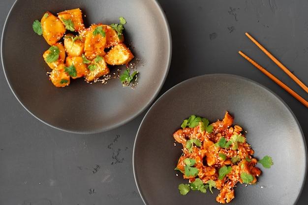 Gebakken kip met pinda's en gefrituurde aubergine in kommen op grijze achtergrond