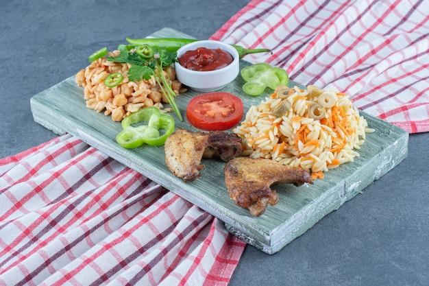 Gebakken kip met rijst en pasta op een houten bord.