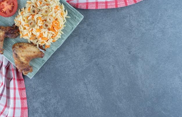 Gebakken kip met rijst op een houten bord.