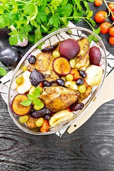 Gebakken kip met tomaten, appels, pruimen en druiven in een glasbrander op een servet, knoflook, peterselie en basilicum op donkere houten plank van bovenaf