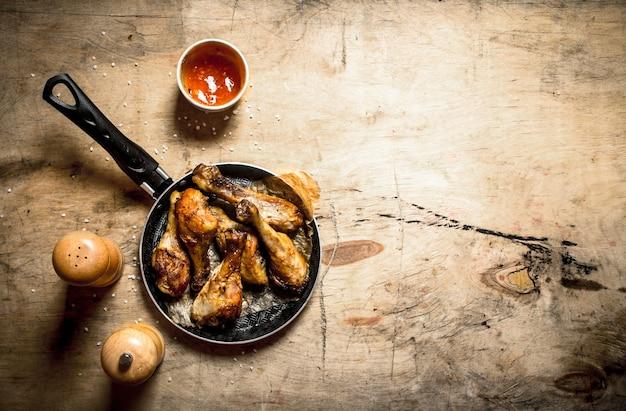 Gebakken kip met tomatensaus. op een houten tafel.