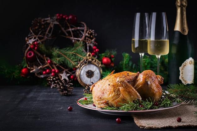 Gebakken kip of kalkoen. de kersttafel wordt geserveerd met kalkoen, versierd met helder klatergoud. gebakken kip, tafel. kerstdiner. tafel opstelling. bovenaanzicht, boven