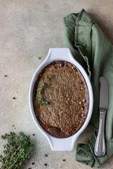 Gebakken kip- of kalkoenleverpastei of soufflé in een keramische vorm met tijm. bovenaanzicht.