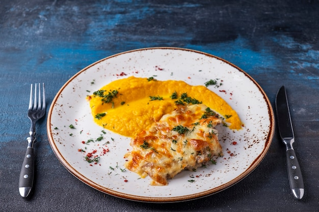 Gebakken kip onder kaas met wortelpuree geserveerd met mes en vork